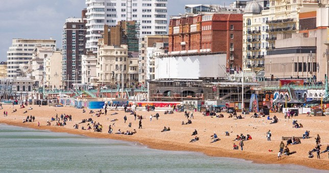 10 happiest cities Mandatory Credit: Photo by Hugo Michiels/LNP/REX/Shutterstock (10228205h) People enjoying the sunshine on the beach in Brighton as colder weather hits the seaside resort Seasonal Weather, UK - 04 May 2019