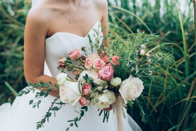 Stock photo of bride in white dress holding bunch of wedding flowers