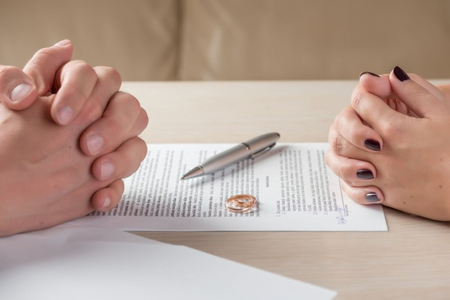 Two pairs of hands on top of divorce paperwork