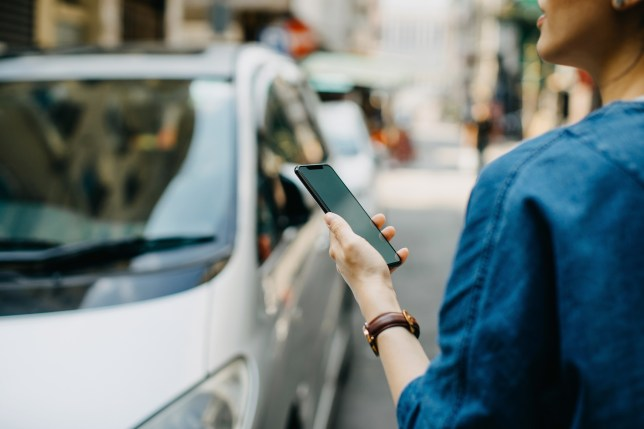 Woman standing in the street, holding a phone and ordering a taxi
