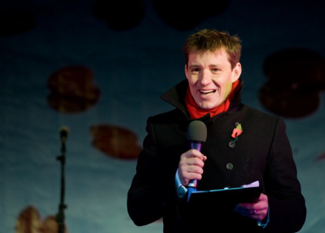 Ben Shephard standing on stage and holding a microphone and a clipboard