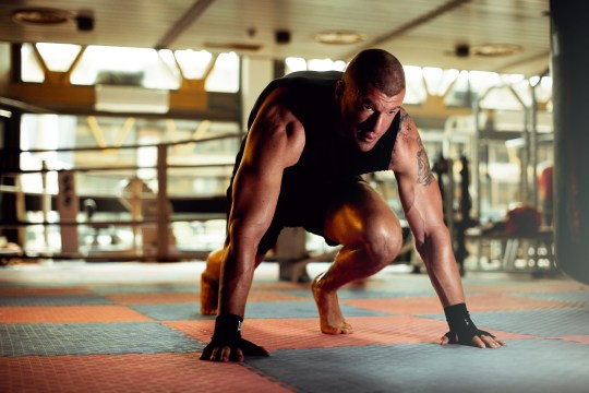 A man doing mountain climbers in the gym