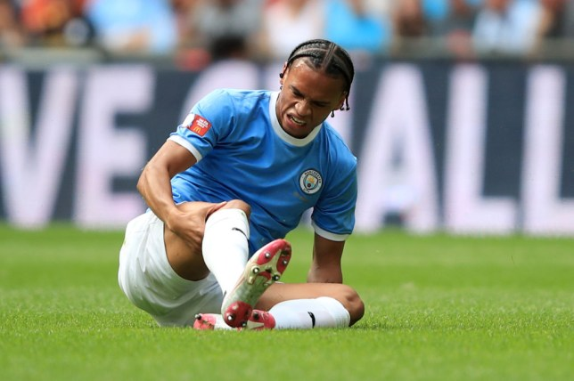 Leroy Sane sits on the ground injured during a Manchester City match against Liverpool