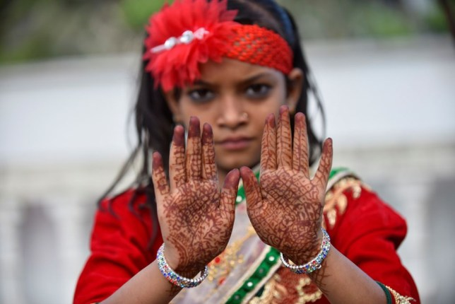 A Nepalese Muslim girl shows her hands as Muslims gather to perform Eid al-Adha prayer
