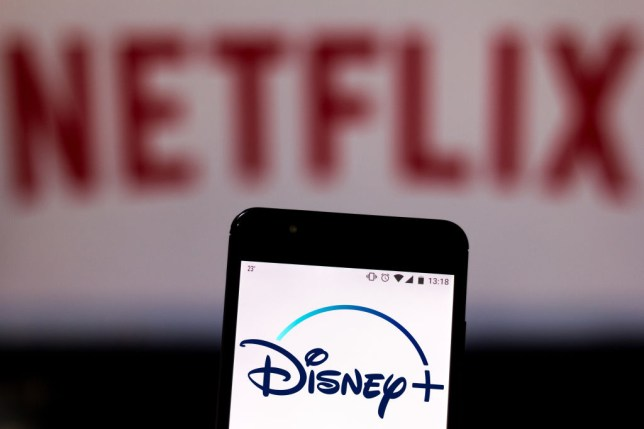 Disney+ logo on a phone in front of the Netflix logo
