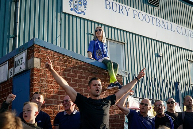 Fans chant songs as they stand outside Bury Football Club's Gigg Lane stadium