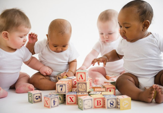 A group of babies playing with blocks