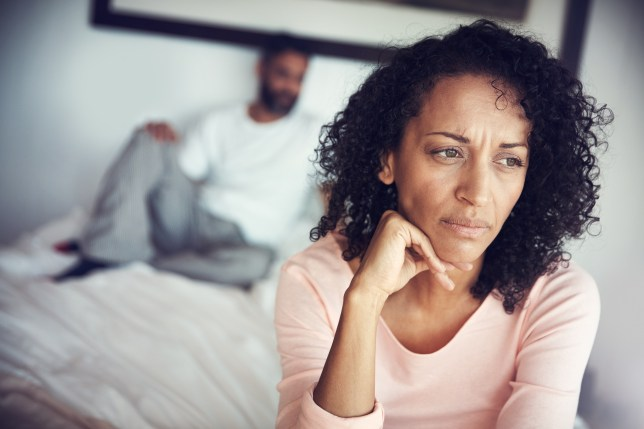A middle aged woman sits on a bed looking upset with her husband in the background
