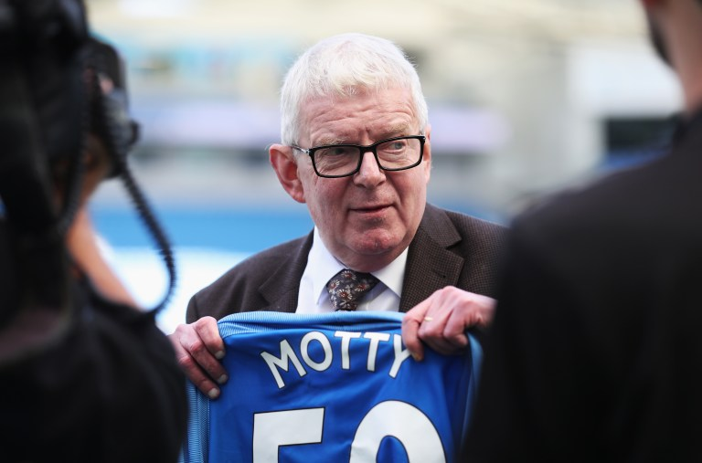 Football commentator John Motson holds up a T-shirt that he is presented with before a Premier League match between Brighton and Hove Albion and West Bromwich Albion at Amex Stadium in 2017
