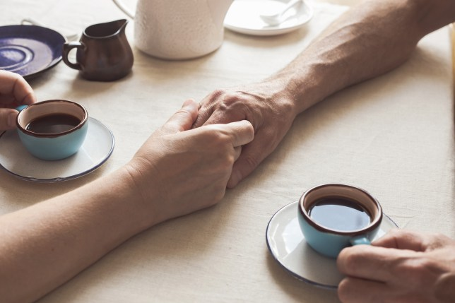 Cropped image of senior couple holding hands and drinking breakfast coffee at home