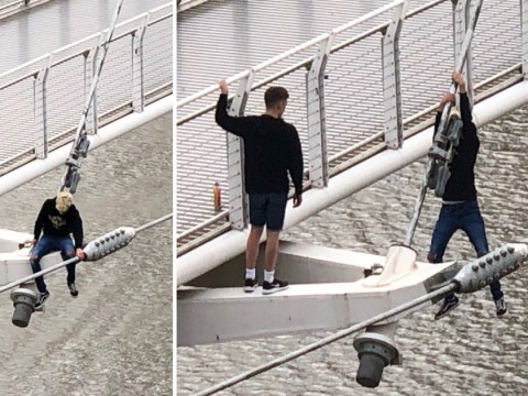 Pair seen dicing with death as they hang from 50ft bridge as high winds rock UK