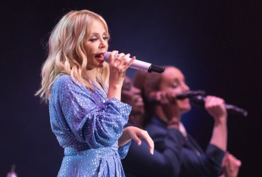 Kylie Minogue wears a purple dress as she performs on stage at Brighton Pride
