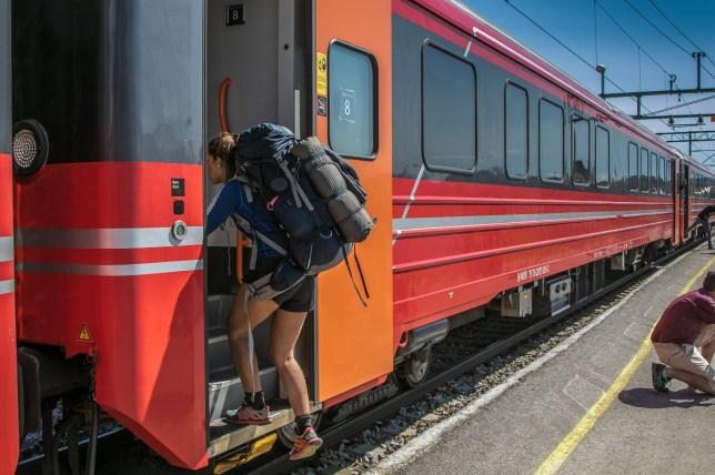 Female hiker is boarding an Oslo - Bergen train in Norway at one of the station near Oslo.