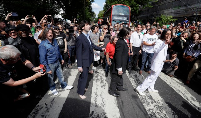 Fans dressed as lookalikes walk across the Abbey Road zebra crossing on the 50th anniversary of British pop musicians the Beatles doing it for their album cover of Abbey Road in St John's Wood in London