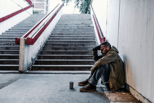 Photo of homeless man sitting in the train station, Subway station, tunnel or underground and asking for help with donation can near him. Side view of Desperate mature man who lost job abandoned and lost in depression sitting on ground street wall suffering emotional pain.