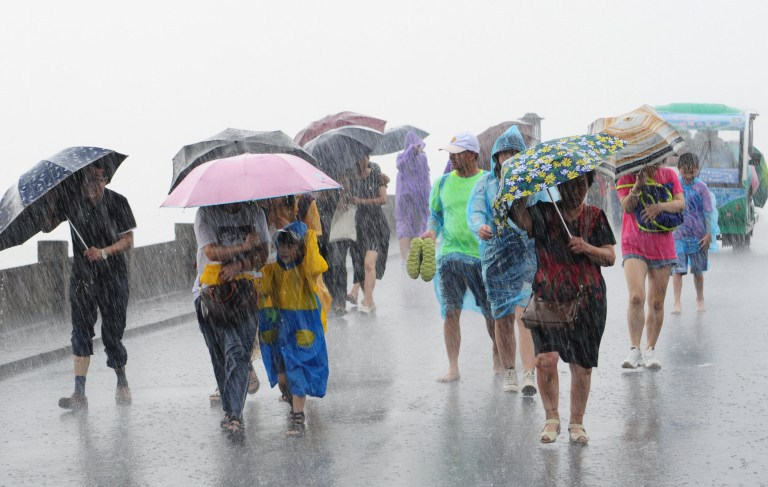 people with umbrellas walk in the rain brought by Typhoon Lekima