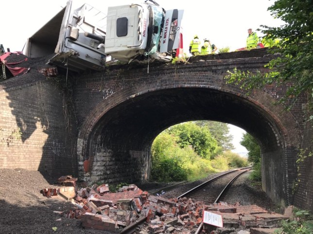 Lorry left hanging over bridge after dramatic crash