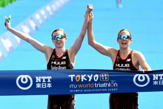 TOKYO, JAPAN - AUGUST 15: Jessica Learmonth (R) and Georgia Taylor Brown (L) of Great Britain cross the finish tape hand-in-hand during the Women's Olympic Qualification event before their disqualification during the ITU Olympic Qualification at Odaiba Marine Park on August 15, 2019 in Tokyo , Japan. (Photo by The Asahi Shimbun via Getty Images)