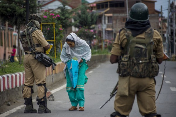 SRINAGAR, KASHMIR, INDIA - AUGUST 17: Indian government forces check the prescriptions of a woman before allowing her to walk towards the hospital, amid curfew like restrictions in the old city, after Indian authorities revoked Article 370 and Article 35A, on August 17, 2019 in Srinagar, the summer capital of Indian administered Kashmir, India. Curfew like restrictions remain in place in Kashmir for the thirteenth consecutive day after India revoked articles 370 and 35A, and phone and internet services also remained suspended. Article 35A of the Indian Constitution was an article that empowered the Jammu and Kashmir state's legislature to define permanent residents of the state and provided special rights and privileges to those permanent residents, also preventing non-locals from buying or owning property in the state. Prior to 1947, Jammu and Kashmir was a princely state under the British Empire. It was added to the Constitution through a Presidential Order. The Constitution Order 1954, (Application to Jammu and Kashmir) was issued by the President of India on 14 May, 1954 in accordance with Article 370 of the Indian Constitution, and with the concurrence of the Government of the State of Jammu and Kashmir. Kashmir has been a state under siege, with both India and Pakistan laying claim to it. Human rights organizations say more than 80,000 have died in the two decade long conflict with the Indian government claiming the number as 42,000. (Photo by Yawar Nazir/ Getty Images)