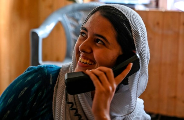 In this photo taken on August 17, 2019, a Kashmiri Muslim looks on as she talks to relatives on a landline phone in Srinagar. - Seventeen out of around 100 telephone exchanges were restored on August 17 in the restive Kashmir Valley, the local police chief told AFP, after an almost two-week communications blackout. (Photo by TAUSEEF MUSTAFA / AFP)TAUSEEF MUSTAFA/AFP/Getty Images