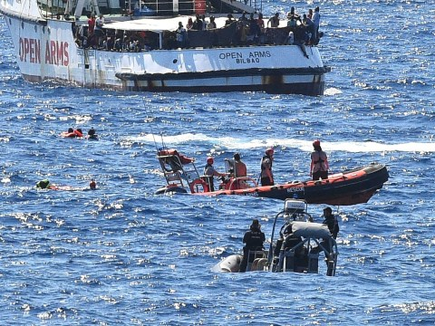 Desperate migrants jump into water to Italian island from stand-off boat