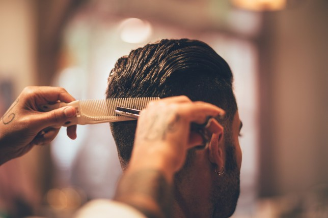 Close-up of barber's tattooed hands holding comb and scissors and giving man trendy hairstyle