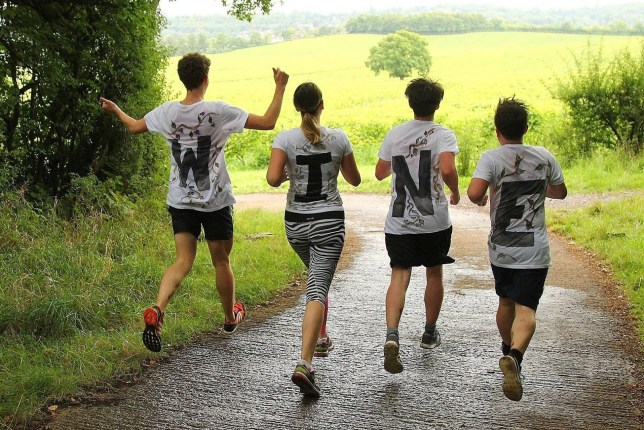Four people running in nature and wearing t-shirts with letters on them that spell out WINE