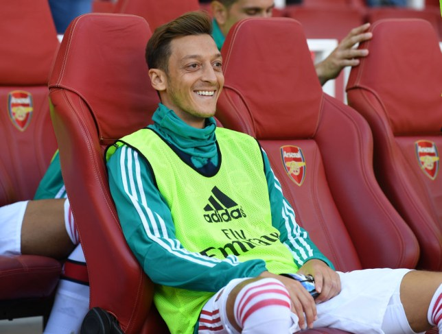 Mesut Ozil smiles on the bench before Arsenal's play against Spurs