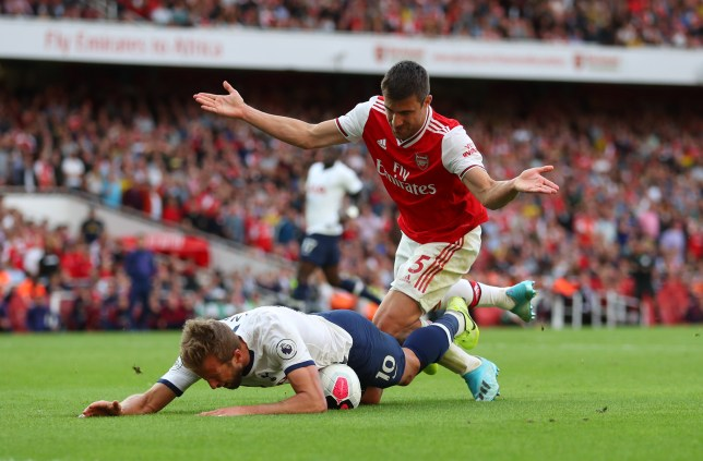 Harry Kane goes down under a challenge from Sokratis