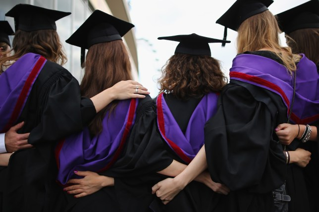 Female university students standing arm in arm