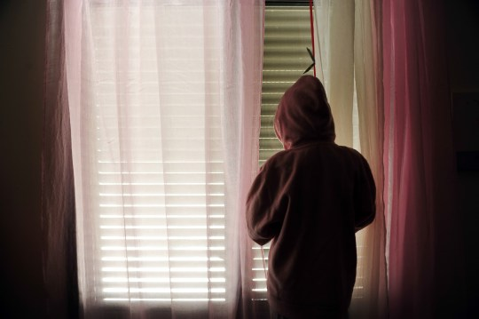 Young girl wearing a hood inside a dark room looking outside from a window with curtains.