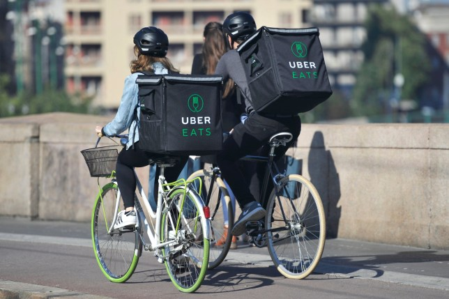Milan - Italy , july22,2018 Uber Eats is an International food delivery company from U.S, Cyclist caring backpacks - home deluvery of food with bike ; Shutterstock ID 1140551222; Purchase Order: -