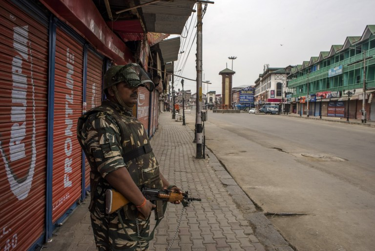 SRINAGAR, KASHMIR, INDIA - AUGUST 30: An armed Indian paramilitary trooper stands guard on August 30, 2019 in Srinagar, the summer capital of Indian administered Kashmir, India. Indian authorities deployed thousands of government forces in Kashmir after India revoked articles 370 and 35A. Journalists continue to face harassment, obstruction and threats and media face a continued communications blackout, as the lockdown continues. Article 35A of the Indian Constitution was an article that empowered the Jammu and Kashmir state's legislature to define permanent residents of the state and provided special rights and privileges to those permanent residents, also preventing non-locals from buying or owning property in the state. Prior to 1947, Jammu and Kashmir was a princely state under the British Empire. It was added to the Constitution through a Presidential Order. The Constitution Order 1954, (Application to Jammu and Kashmir) was issued by the President of India on 14 May, 1954 in accordance with Article 370 of the Indian Constitution, and with the concurrence of the Government of the State of Jammu and Kashmir. Kashmir has been a state under siege, with both India and Pakistan laying claim to it. Human rights organizations say more than 80,000 have died in the two decade long conflict with the Indian government claiming the number as 42,000. (Photo by Yawar Nazir/ Getty Images) (