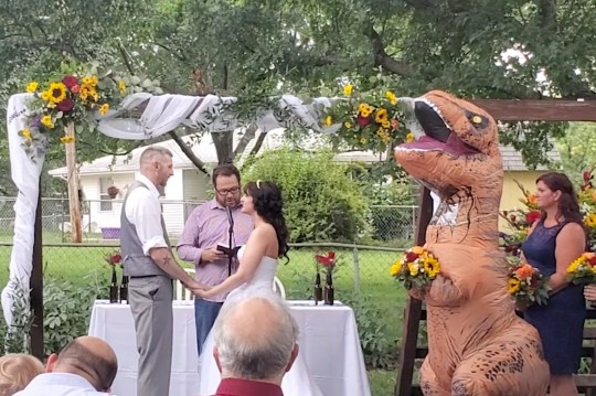 PIC FROM Caters News - (PICTURED: Footage showing Christina Meador wearing a T-Rex costume to her sisters wedding ceremony in Omaha, Nebraska on August 10th) - A quirky maid of honour stole the show when she turned up to her sisters wedding dressed in a T-Rex costume.When Deanna Adams, 40, and her 34-year-old fianc? Joby tied the knot on August 10 in Omaha, Nebraska, they didn't think there would be much to overshadow their big day.Enter sister of the bride Christina Meador, 38, who came walking through the house wearing one of the inflatable dinosaur costumes.SEE CATERS COPY