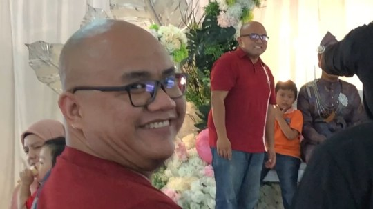 Two bald men at a wedding wearing same outfit, red tshirt, black glasses