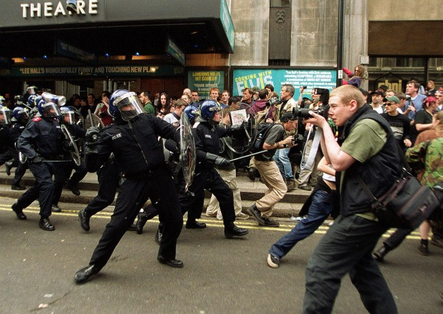 LONDON, UNITED KINGDOM - MAY 1: Riot Police charge protesters at Whitehall in central London after violence broke out near a Mcdonalds fast food restaurant during a May Day anti-capitalist rally 01 May 2000. Protesters had already attacked police with bottles and bricks prior to their charge. (Photo credit should read HUGO PHILPOTT/AFP/Getty Images)
