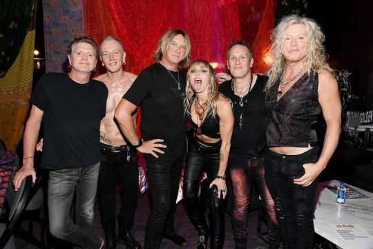 LAS VEGAS, NEVADA - SEPTEMBER 21: (EDITORIAL USE ONLY) Rick Allen, Phil Collen, Joe Elliott, Miley Cyrus, Vivian Campbell, and Rick Savage of Def Leppard attend the 2019 iHeartRadio Music Festival at T-Mobile Arena on September 21, 2019 in Las Vegas, Nevada. (Photo by Kevin Mazur/Getty Images for iHeartMedia)