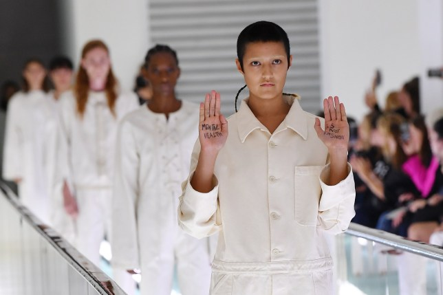 Gucci model protests during Milan fashion week show featuring straitjackets