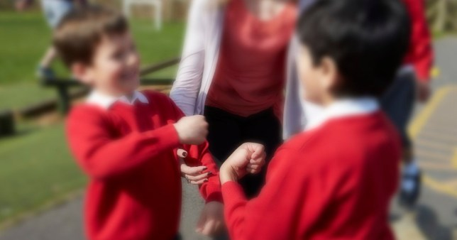 Female Teacher Stopping Two Boys Fighting In Playground