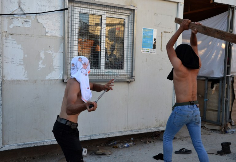 epa07880623 Migrants attack a housing facility during a fire that broke out in the refugee camp of Moria in Lesvos island, Greece 29 September 2019. Two people have died at the fire that broke out 29 September afternoon at the Moria reception and identification center, according to the latest information released by Greek Police headquarters. An upheaval is reported at the Moria refugee camp, following a fire that broke out shortly after 5 pm on 29 Septembe in a container box at one of the accommodation compounds, which then spread to another seven housing units. Moria was evacuated to allow for the intervention of the fire brigade, while the camp director and the police are gathering information to decipher the cause of the fire. Scuffles between the police and the camp's residents are also reported to be unfolding. EPA/STRATIS BALASKAS