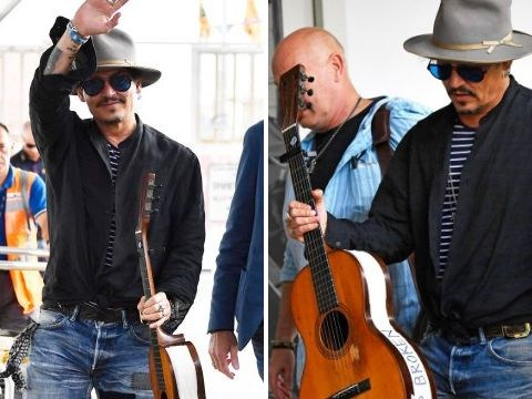 Johnny Depp clutches broken guitar after Venice Film Festival appearance and we have so many questions