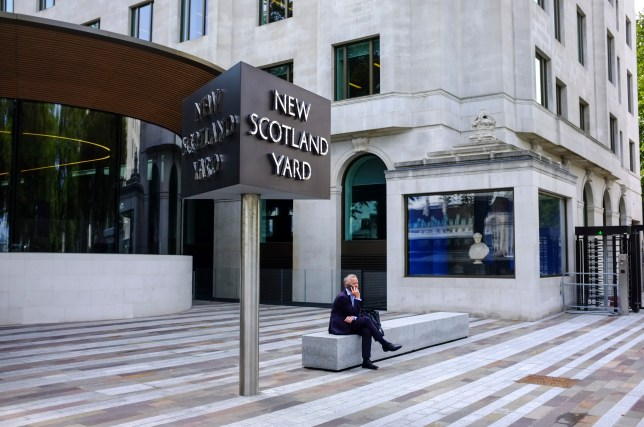 A man sits on the phone under the New Scotland Yard sign