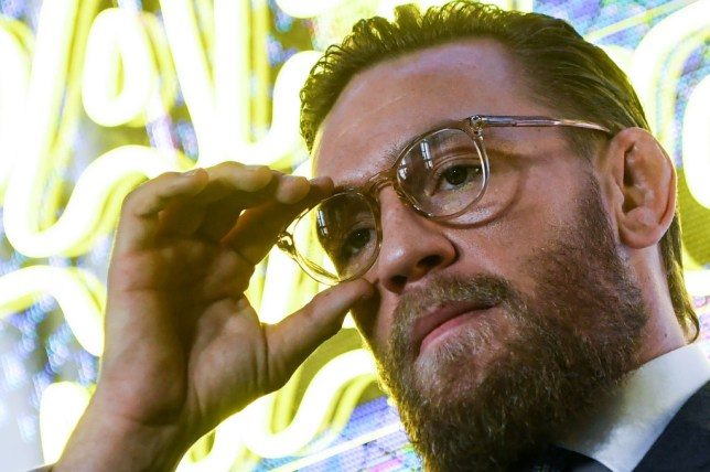 Conor McGregor adjusts his glasses at a press conference in Russia