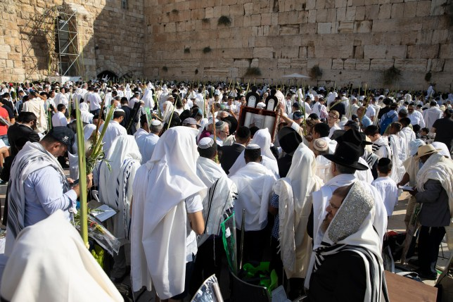 Jewish people celebrating Sukkot at the Western Wall in Jerusalem