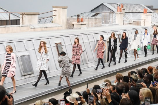 PARIS, FRANCE - OCTOBER 01: A spectator from the audience climbs the runway to walk with the models during the finale of the Chanel Womenswear Spring/Summer 2020 show as part of Paris Fashion Week on October 1, 2019 in Paris, France. (Photo by Victor Boyko/Getty Images)
