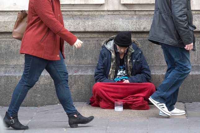 A homeless person sits outside Victoria Station in London, which has the highest number of homeless deaths anywhere in the country, according to a new report which shows the highest rise in deaths since records began.