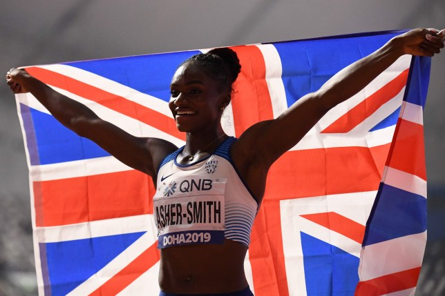 Britain's Dina Asher-Smith holds the national flag after winning the Women's 200m final at the 2019 IAAF Athletics World Championships at the Khalifa International stadium in Doha on October 2, 2019. (Photo by Jewel SAMAD / AFP) (Photo by JEWEL SAMAD/AFP via Getty Images)