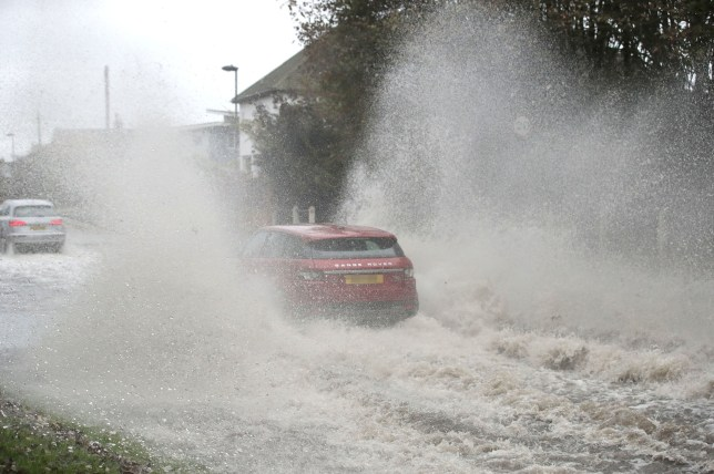 Car going through a flooded street in Whitley Bay in Northumberland. A slow-moving band of heavy rain set to drench parts of the UK has triggered weather warnings and flood alerts. PA Photo. Picture date: Sunday October 6, 2019. The Met Office has issued two yellow warnings of rain for Sunday that it predicts could bring transport disruption and flooding. See PA story WEATHER Rain. Photo credit should read: Owen Humphreys/PA Wire