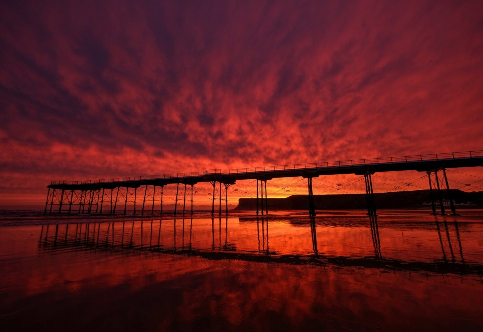 SALTBURN BY THE SEA, ENGLAND - OCTOBER 07: A brief but fiery sunrise rises behind Saltburn pier and cliffs on October 07, 2019 in Saltburn By The Sea, England. Heavy rain in the west will gradually push further east as the day progresses. (Photo by Ian Forsyth/Getty Images)