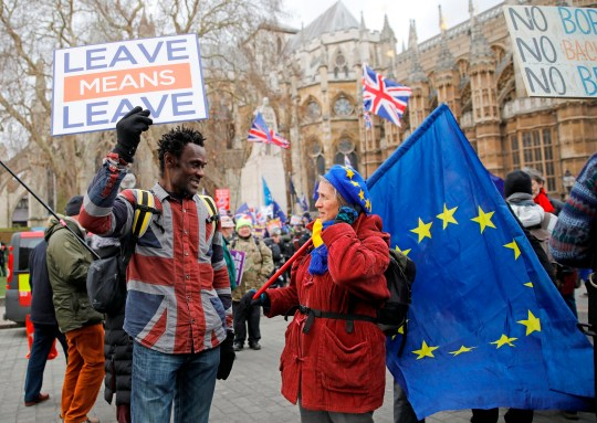 A pro-Brexit activist (L) holding a placard and wearing a union flag-themed shirt talks with an anti-Brexit demonstrator holding an EU flagas they protest near the Houses of Parliament in London on January 29, 2019.